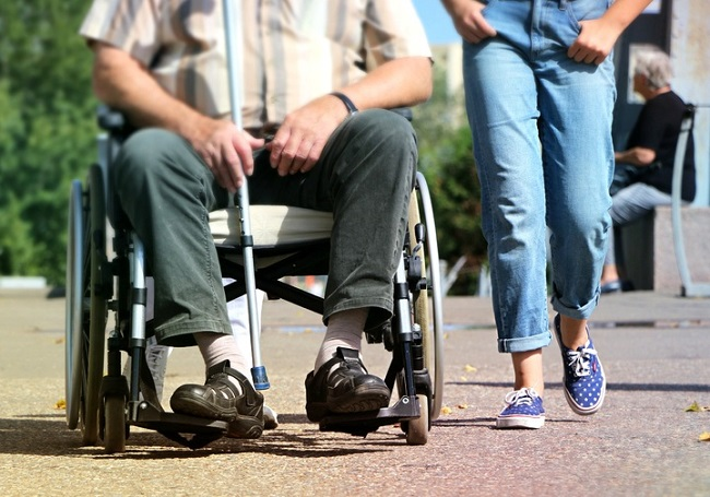 man on a wheelchair being wheeled over resin gravel by two helpers